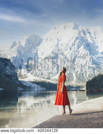 Lago Di Braies. Beautiful Girl In A Red Dress On The Lake Braies (lago Di Braies) In Dolomites Mount