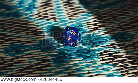 Close-up Image Of A Blue 20-sided Role-playing Gaming Die On An Eastern-inspired Carpet In The Sun