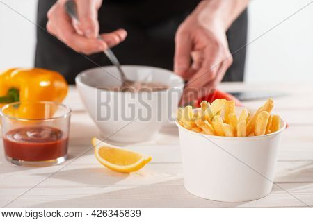 A Backet Of French Fries, Vegetables, Lemon And Ketchup