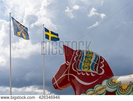 A Horizontal View Of A Colorful Swedish Dala Horse And The Swedish Flag Under An Expressive Sky