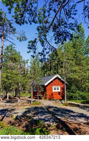 A Vertical View Of An Idyllic Wooden Red Cottage In Forest Landscape On The Baltic Sea In Northern S