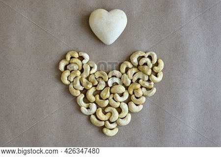 Heart Made Of Cashew Nuts And Souvenir Stone Heart On Gray Craft Paper. Top View. Close-up. Copy Spa