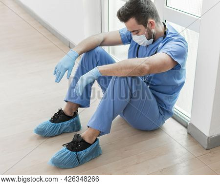 Male Nurse Tired After Long Shift Hospital 2. High Quality Beautiful Photo Concept