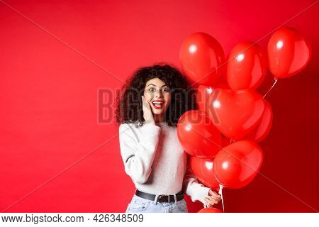 Valentines Day. Surprised Curly-haired Girl Holding Heart Balloons And Looking Amazed At Camera, Rec