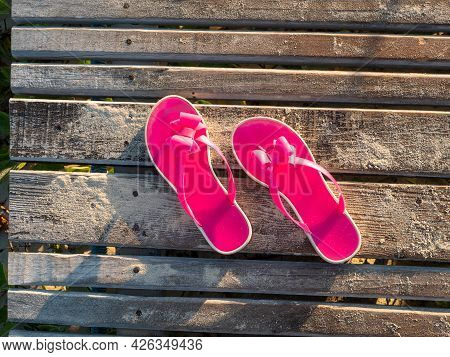 Beach Pink Bright Slippers Stand On A Wooden Platform Near The Ocean. Close-up Of Slippers From Abov