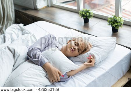 Photo Of A Sleeping Woman. She Lies Under The Covers And Hugs The Pillow.