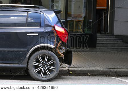 Old Broken Car On A City Street. The Car Hit In The Bumper Is Parked By The Road. The Impact Site Is