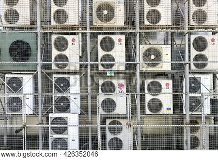 Lots Of Air Conditioners On The Wall Of The Building Covered With The Metal Grid. There Are Lg, Daik