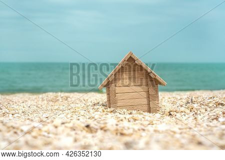 Real Estate Or House By The Sea Concept With A Little Wooden House On The Sand Against The Seascape.
