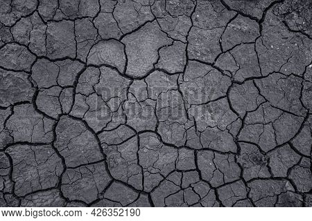 Drought And Soil Dehydration Background. Dry Cracked Earth Texture. Toned Image.
