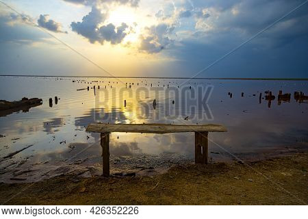Wooden Bench By The Lake At Sunset. Beautiful Landscape.
