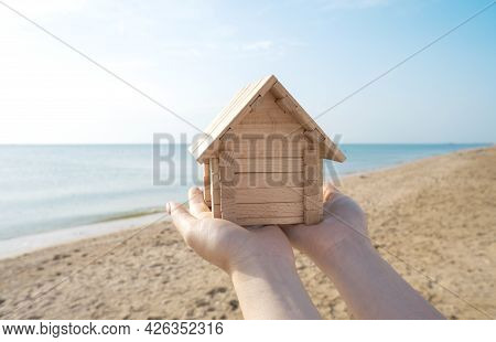 Residential Property Or Real Estate By The Sea Concept With A Small Wooden House In Female Hands Aga