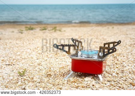 Tourist Gas Burner On The Beach. Portable Travel Gas Hob. Background With Copy Space.