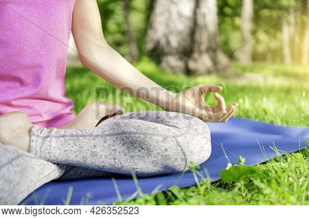 Reuniting With Nature And Zen Concept. Girl Practicing Yoga In A City Park. Yoga Lotus Position. Wom