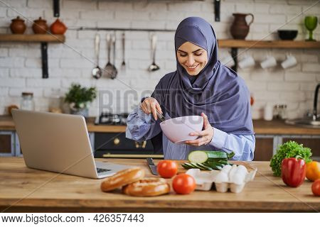 Arabian Woman Cooking A Meal And Having A Video Call On A Laptop