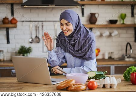 Arabian Woman Waving During A Video Call On A Laptop And Cooking In The Kitchen