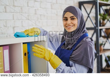 Portrait Of A Gorgeous Muslim Woman Cleaning Shelves With Books