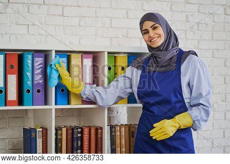 Cheerful Arabian Woman Wiping Dust Off The Bookshelves