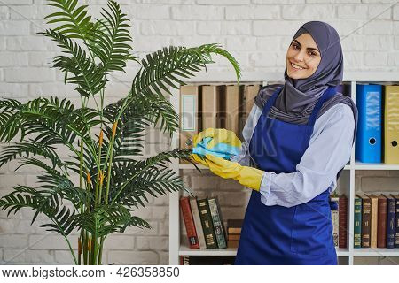 Beautiful Arabian Woman Cleaning Leaves Of A Plant In The Office
