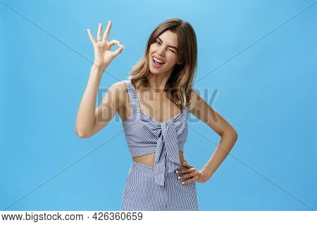 Cute Charismatic Woman With Gap Teeth Showing Okay Gesture Tilting Head Joyfully, Holding Hand On Wa