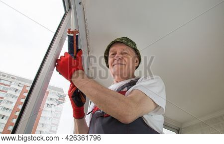 A Master Builder Standing Under The Ceiling Of The Loggia In Red Gloves With A Sealant In His Hands.