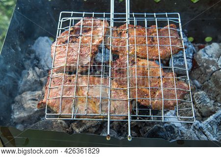 Meat Steaks Fried In A Metal Grill Against The Background Of Smoldering Coals In The Grill. Cooking