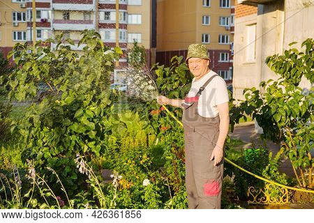 A Gardener In Overalls With A Yellow Hose Watering Flowers Against The Background Of Apartment Build
