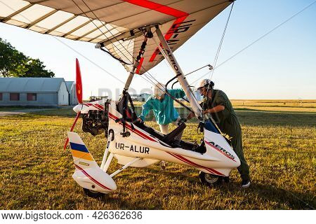 Odessa, Ukraine - July 14, 2016: Pilot Preparing Young Woman For The Flight At Motor Hang Glider At