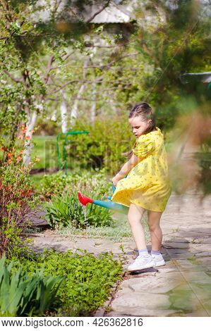 A Six-year-old Child In A Dress Swaying In The Wind Waters Flowers From A Garden Watering Can Surrou