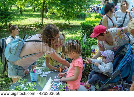Zaporizhia, Ukraine- June 19, 2021: Charity Family Festival:  Children Painting Funny Paper   Figure
