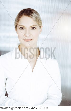 Friendly Adult Business Woman Standing Straight. Business Headshot Or Portrait In Sunny Office