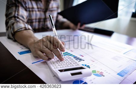 Finance And Accounting Concept. Close Up Businessman Using Calculator For Do Math Finance And Readin