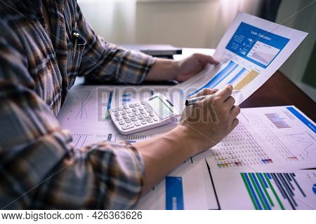 Bookkeeper Examine Company Performance On Table With Profit Document, Earnings, Income And Loss. Fin