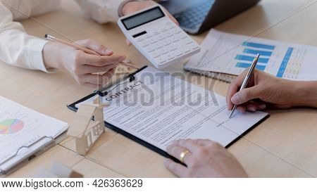Realtor Agent Or House Seller Showing Price Of House On Calculator And Pointing To The Signature Poi