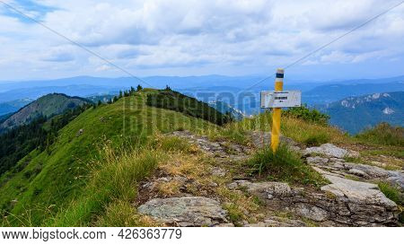 Terchova, Slovakia - July 3, 2021: The Kraviarske (1361 M) Peak Sign With A View Of The Surrounding