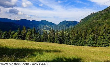 Beautiful View Of A Green Mountain Meadow With Mountain Ridge And Blue Cloudy Sky In The Background.