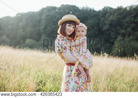 Portrait Of Pleasant Smiling Mom With Little Cute Baby Girl Together On Nature On Summer Day. Young
