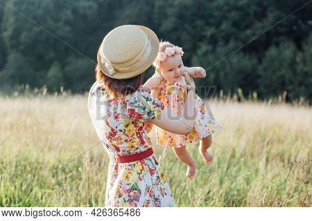 Mom And Cute Little Daughter Playing At Field, Circling With Baby In The Field. A Mother Walks With