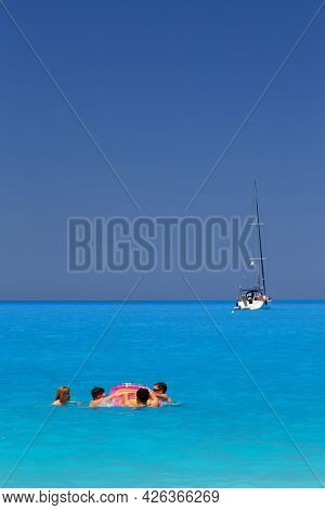 Myrtos Beach, Cephalonia Island, Greece - July, 13 2019: A Family With Children Swimming And Playing
