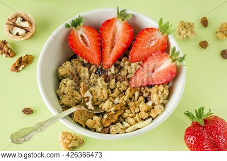 Healthy Breakfast In A White Bowl With Natural Granola. Homemade Baked Muesli, Nuts, Fresh Strawberr