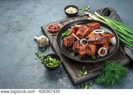 Shish Kebab On A Plate With Onions And Herbs On A Dark Gray Background. Side View, Space For Copying