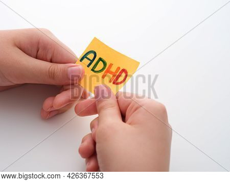Adhd. A Child Holding A Yellow Paper Note In His Hands With The Abbreviation Adhd On It. Close Up. A