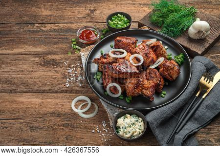 Fried Meat, Barbecue In A Black Plate With Fresh Herbs On A Brown, Wooden Background. Side View, Spa