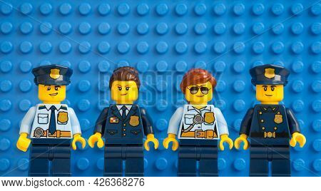Tambov, Russian Federation - July 05, 2021 Four Lego Police Officers Standing In A Row Against Blue