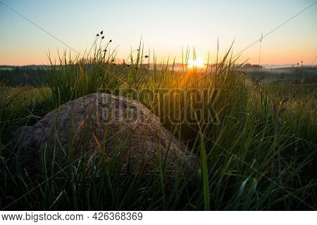 Sunrise Landscape With Roks On The Siede Of The Meadow And Field. Summertime Scenery Of Northern Eur