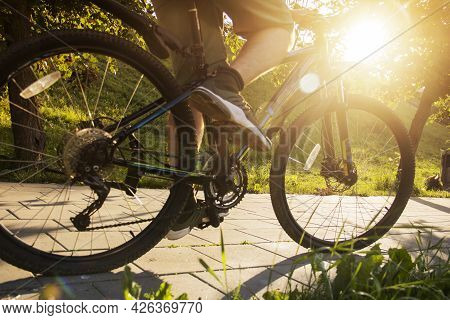 A Man On A Bicycle. Bicycle Wheels Close-up. The Foot Is On The Bicycle Pedal. Active Summer