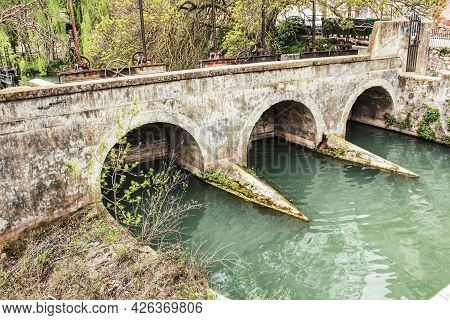 The Jucar River And Old Stone Bridge Surrounded By Vegetation In Alcala Del Jucar Village