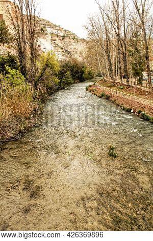 The Jucar River Surrounded By Vegetation In Alcala Del Jucar Village