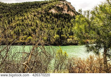 Tolosa Reservoir Surrounded By Vegetation And Mountains In Alcala Del Jucar Village, Albacete, Spain