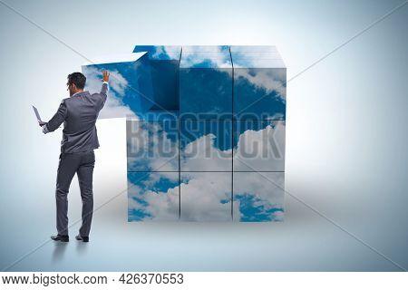 Businessman building cloud cube with shapes